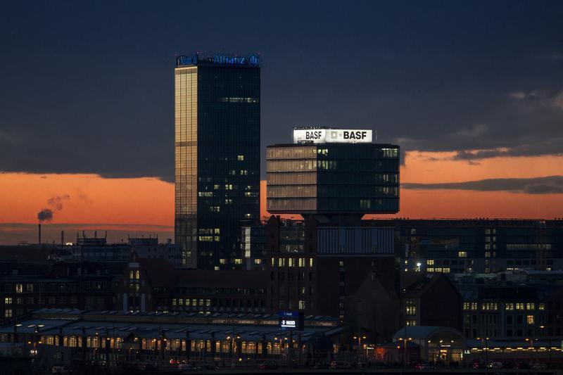 Buildings with neon advertising signs of the German insurer Allianz and chemical company BASF during sunrise in Berlin