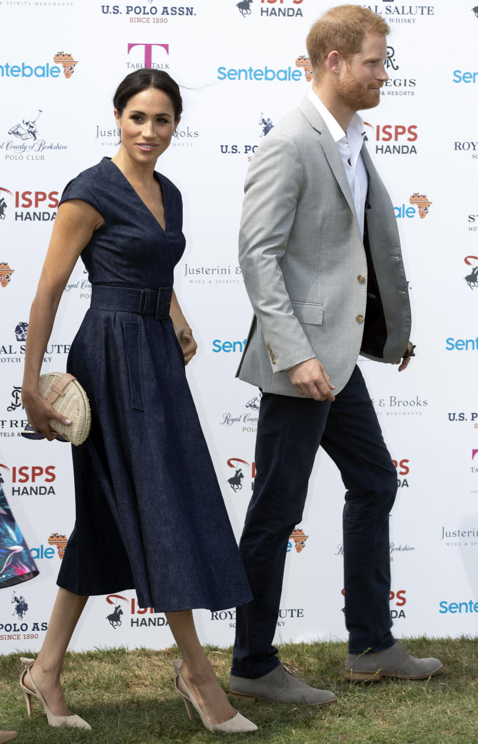 <p>For a surprise appearance at the Sentebale charity polo match on 26 July, the Duchess of Sussex wore a denim midi dress by Carolina Herrera. She teamed the heatwave-appropriate look with a pair of Aquazurra heels, a J Crew clutch and Tom Ford sunnies.<em> [Photo: PA]</em> </p>