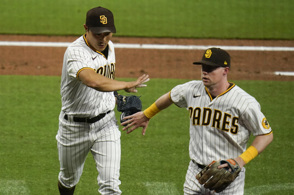 San Diego Padres shortstop Ha-Seong Kim, left, is greeted by teammate second baseman Jake Cronenworth during the second inning of a baseball game against the Pittsburgh PiratesTuesday, May 4, 2021, in San Diego. (AP Photo/Gregory Bull)