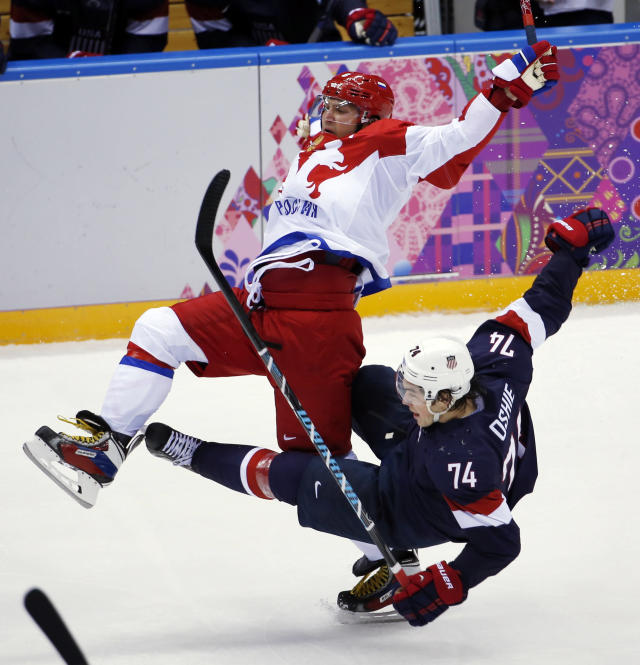 Russia forward Alexander Ovechkin is upended by USA forward T.J. Oshie in the third period of a men's ice hockey game at the 2014 Winter Olympics, Saturday, Feb. 15, 2014, in Sochi, Russia. (AP Photo/Petr David Josek)
