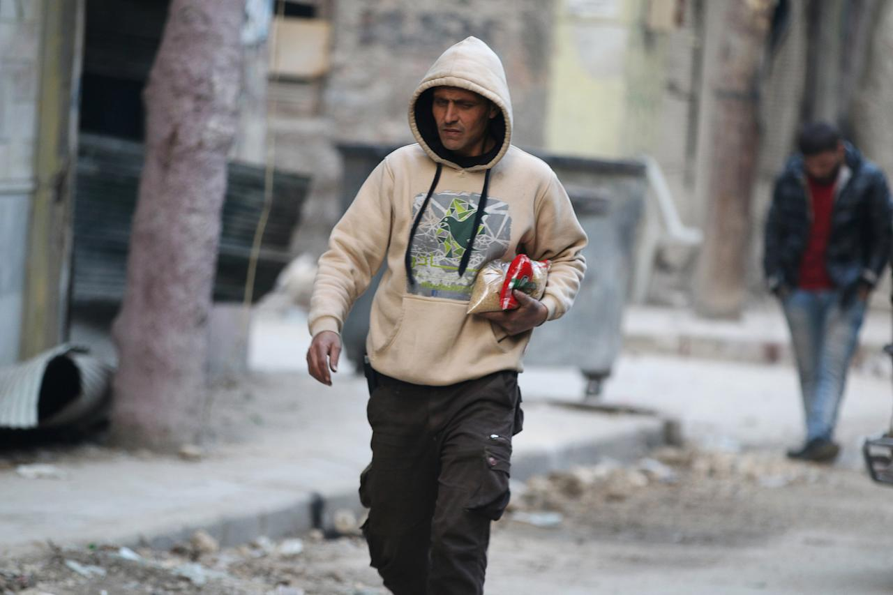 A man carries food as he walks along a street in a rebel-held besieged area of Aleppo, Syria December 10, 2016. REUTERS/Abdalrhman Ismail
