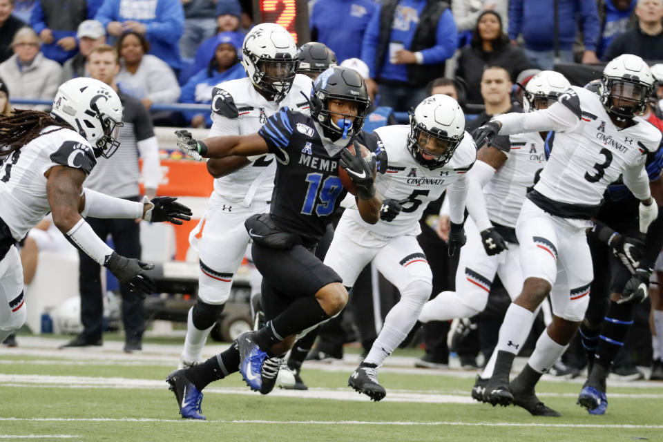 FILEm - Memphis running back Kenneth Gainwell (19) carries the ball against Cincinnati in the first half of an NCAA college football game in Memphis, Tenn., in this Friday, Nov. 29, 2019, file photo. Gainwell had every intention of playing football with the Memphis Tigers last fall, going through fall practice. The funeral for an uncle, the fourth member of his family to die of COVID-19 made opting out of the season the best decision for Gainwell. (AP Photo/Mark Humphrey, File)