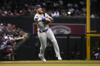 Los Angeles Dodgers third baseman Justin Turner makes an off-balance throw for the out on a ball hit by Arizona Diamondbacks' Nick Ahmed during the seventh inning of a baseball game Friday, July 30, 2021, in Phoenix. (AP Photo/Rick Scuteri)