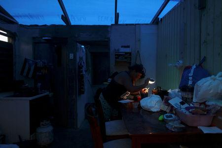 A woman uses a flashlight while trying to connect a transformer to a car battery, in Maunabo