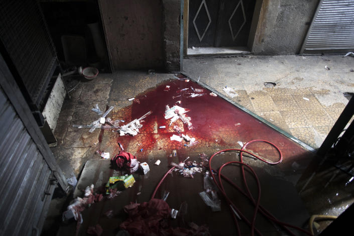 In this Thursday, Oct. 11, 2012 photo, blood and used medical supplies spill out of the back door of Dar al-Shifa hospital in Aleppo, Syria. (AP Photo/Manu Brabo)