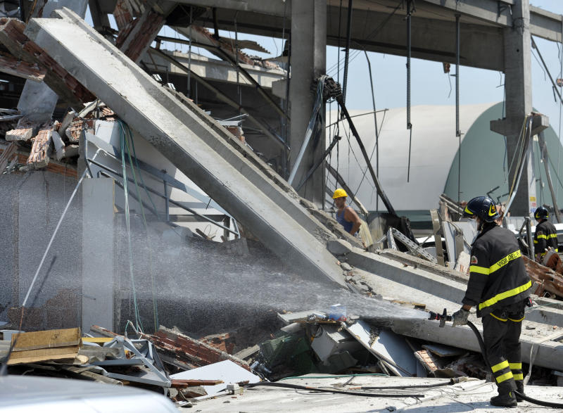 Italian firefighter sprays water on debris of a collapsed factory in Mirandola, northern Italy, Tuesday, May 29, 2012. A magnitude 5.8 earthquake struck the same area of northern Italy stricken by another fatal tremor on May 20. (AP Photo/Marco Vasini)