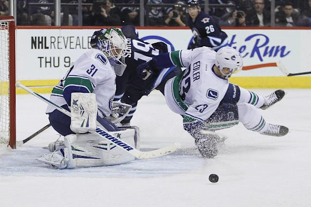 Winnipeg Jets' Jim Slater (19) and Vancouver Canucks' Alexander Edler (23) collide as goaltender Eddie Lack (31) saves the shot from Slater during the second period of an NHL hockey game Wednesday, March 12, 2014, in Winnipeg, Manitoba. (AP Photo/The Canadian Press, John Woods)