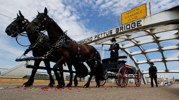 PHOTO: The casket of Rep. John Lewis moves over the Edmund Pettus Bridge by horse drawn carriage during a memorial service for Lewis, July 26, 2020, in Selma, Ala. (John Bazemore/AP)