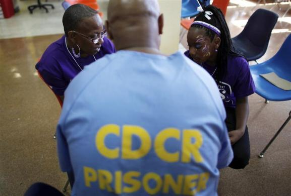 Troyanna (R), 10, sits with her mother Zunknie, 38, as she meets her father Troy, 49, for the first time at San Quentin state prison in San Quentin, California June 8, 2012.