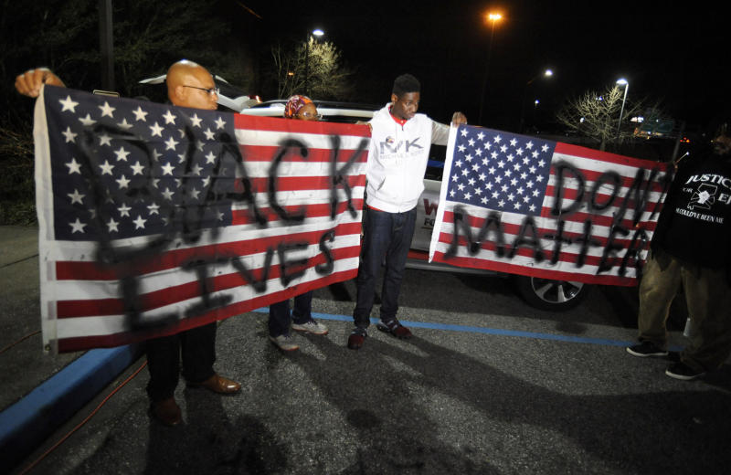 "Activists protesting the police shooting of a black man in an Alabama shopping mall hold U.S. flags painted with the words ""Black lives don't matter"" in Hoover, Ala., Tuesday, Feb. 5, 2019. Demonstrators are upset with the state's decision against prosecuting a police officer who shot and killed Emantic ""EJ"" Bradford Jr. in a shopping mall on Thanksgiving night. (AP Photo/Jay Reeves)"