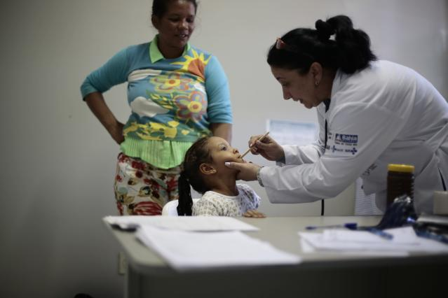 Cuban doctor Dania Rosa Alvero Pez examines a young patient at the Health Center in the city of Jiquitaia in the state of Bahia, north-eastern Brazil, November 18, 2013. They were heckled and called slaves of a communist state when they first landed, but in the poorest corners of Brazil the arrival of 5,400 Cuban doctors is being welcomed as a godsend. The program to fill gaps in the national health system with foreign doctors, mainly from Cuba, could become a big vote-winner for President Dilma Rousseff as she eyes a second term in next year's election despite fierce opposition from Brazil's medical class. Picture taken November 18, 2013. To match story BRAZIL-DOCTORS/CUBA REUTERS/Ueslei Marcelino (BRAZIL - Tags: POLITICS HEALTH)