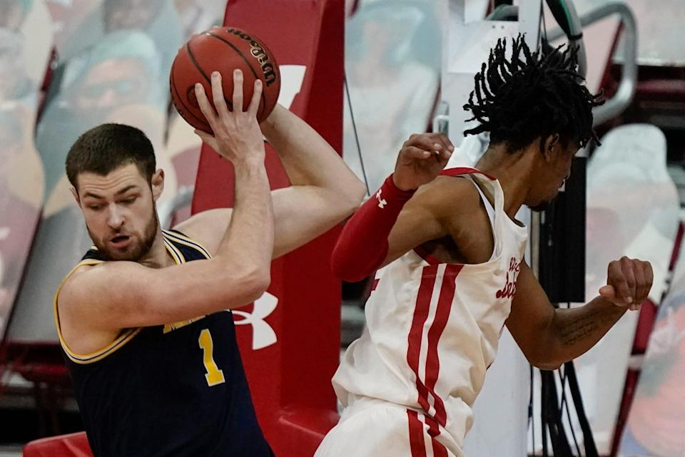 Michigan's Hunter Dickinson gets past Wisconsin's Aleem Ford during the first half Sunday, Feb. 14, 2021, in Madison, Wis.