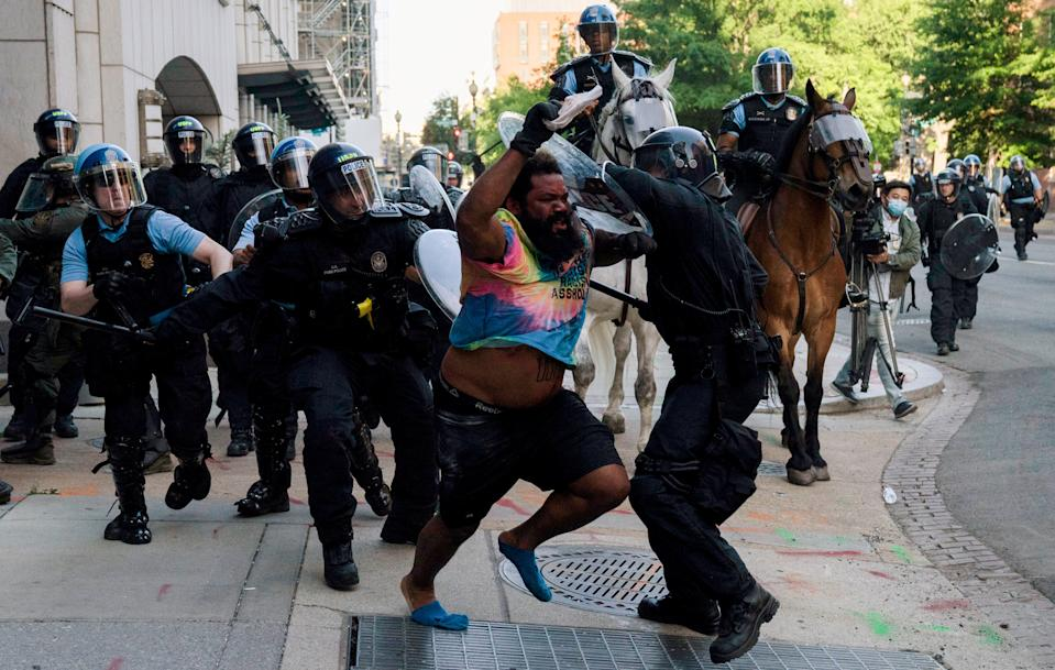 Riot police chase a man as they forcefully clear protestors from Lafayette Park and the surrounding area across from the White House, during a rally against the police killing of George Floyd in Minneapolis, so that President Trump could walk through for a photo opportunity in front of St. John's Episcopal Church on June 1, 2020. (Ken Cedeno/Reuters)
