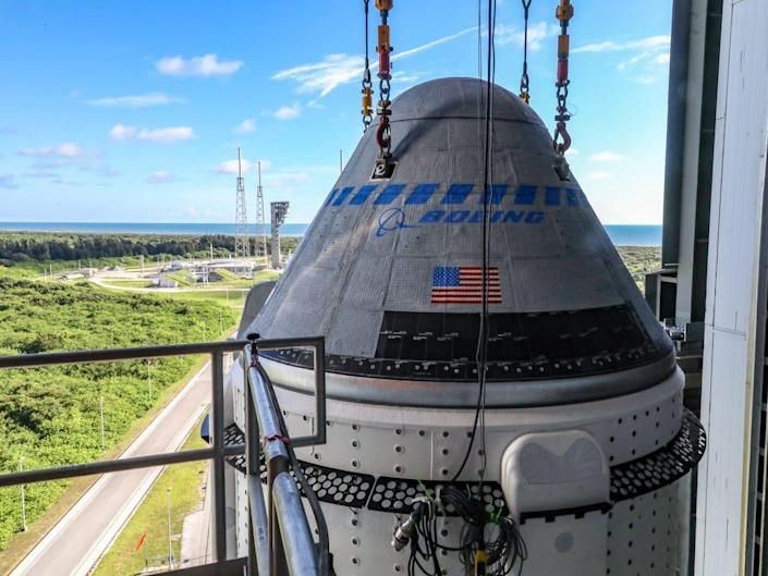 boeing starliner space capsule lowered on cables to rocket