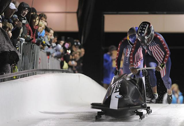 PARK CITY, UT - OCTOBER 25: Bobsled pilot Jazmine Fenlator and brakewoman Lolo Jones push their sled at the start of their first run during the selection runs at the Utah Olympic Park October 25, 2013 in Park City, Utah. With a combined two-run time of 1:39.92, they placed third. (Photo by Gene Sweeney Jr/Getty Images)