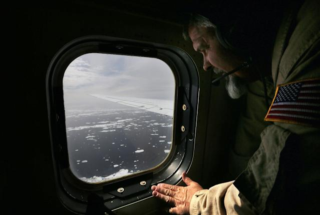 <p>Lyn Lohberger of NASA looks out as sea ice floats near the coast of West Antarctica from a window of a NASA Operation IceBridge airplane on October 27, 2016 in-flight over Antarctica. (Photo: Mario Tama/Getty Images) </p>