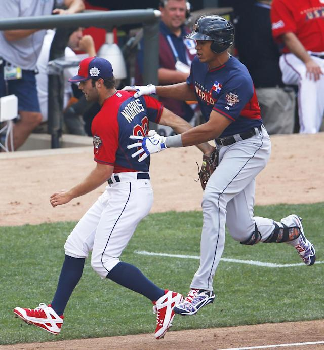 United States' pitcher Daniel Norris, left, forces out World's Steven Moya, right, at first base during the second inning of the All-Star Futures baseball game, Sunday, July 13, 2014, in Minneapolis. (AP Photo/Paul Sancya)