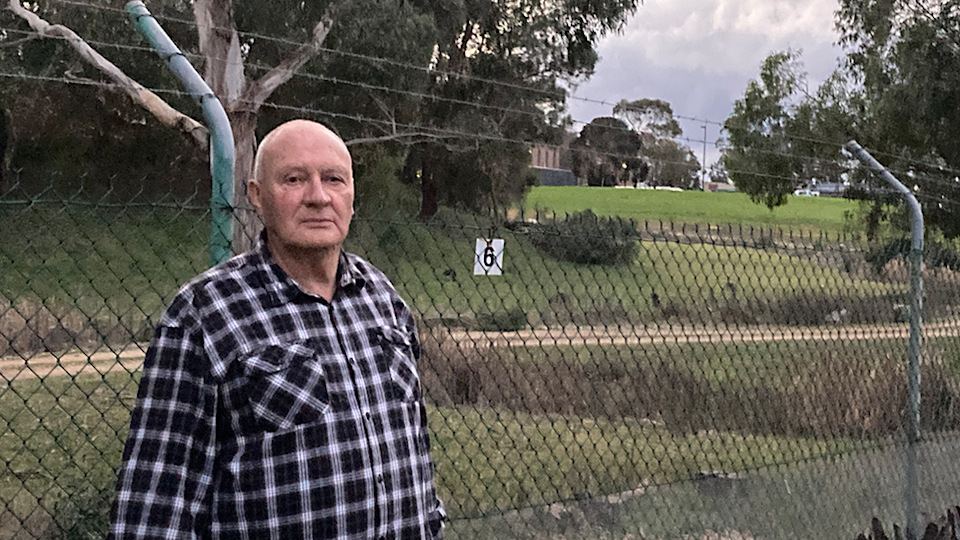 Ian Fairweather's stands in front of the fence at the edge of his backyard.