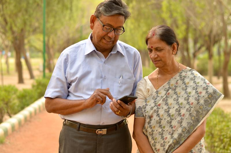 Senior retired man and woman couple in park looking at their smart phone and laughing in Delhi, India