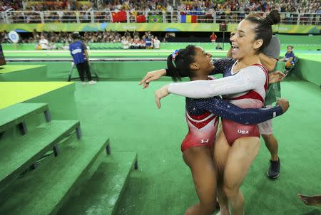 Simone Biles hugs team mate Alexandra Raisman following her floor routine during the women's team final. REUTERS/Mike Blake
