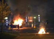 A man walks past a burning car that was hijacked by Loyalists at the Cloughfern roundabout in Newtownabbey, Belfast, Northern Ireland, Saturday April 3, 2021. Masked men threw petrol bombs and hijacked cars in the Loyalist area North of Belfast. Loyalists and unionists are angry about post-Brexit trading arrangements which they claim have created barriers between Northern Ireland and the rest of the UK. (Peter Morrison/PA via AP)