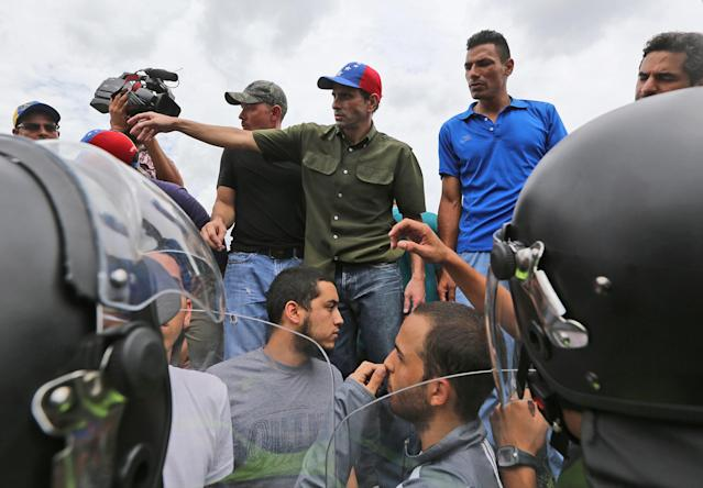 <p>Opposition leader Henrique Capriles, center, stands on Francisco Fajardo highway, lined by police, during a protest in Caracas, Venezuela, June 7, 2016. (AP/Fernando Llano) </p>