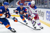 New York Rangers' Brendan Smith, right, passes away from New York Islanders' Brock Nelson, left, and Josh Bailey, center, during the second period of an NHL hockey game Sunday, April 11, 2021, in Uniondale, N.Y. (AP Photo/Frank Franklin II)
