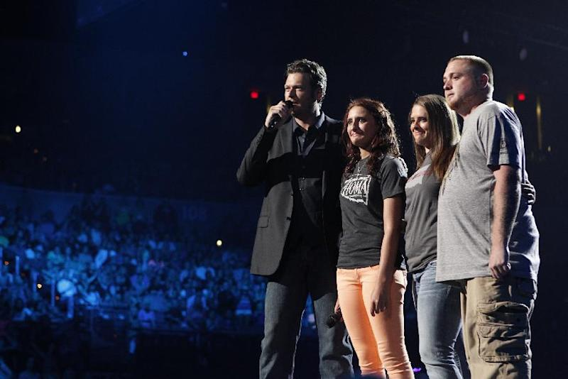This image released by NBC Universal shows country singer Blake Shelton, left is shown on stage with Alyson Costilla, second left, 18, and her family during the Healing in the Heartland: Relief Benefit Concert at the Chesapeake Energy Arena in Oklahoma City, Okla., Wednesday, May 29,2013. Funds raised by the benefit will go to the United Way of Central Oklahoma, for recovery efforts for those affected by the May 20 tornado. Costilla lost her mother Terri Long in the storm. (AP Photo/NBC, Trae Patton)