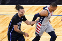 Orlando Magic guard Cole Anthony, left, jokes with Washington Wizards guard Russell Westbrook after Anthony was called for goaltending on a Westbrook shot during the second half of an NBA basketball game Wednesday, April 7, 2021, in Orlando, Fla. (AP Photo/John Raoux)