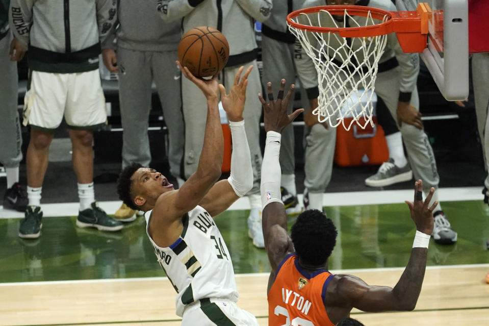 Milwaukee Bucks forward Giannis Antetokounmpo (34) shoots over Phoenix Suns center Deandre Ayton, right, during the second half of Game 4 of basketball's NBA Finals in Milwaukee, Wednesday, July 14, 2021. (AP Photo/Paul Sancya)