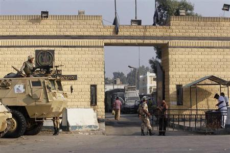 Egyptian army soldiers guard with armoured personnel carriers in front of the main gate of Torah prison