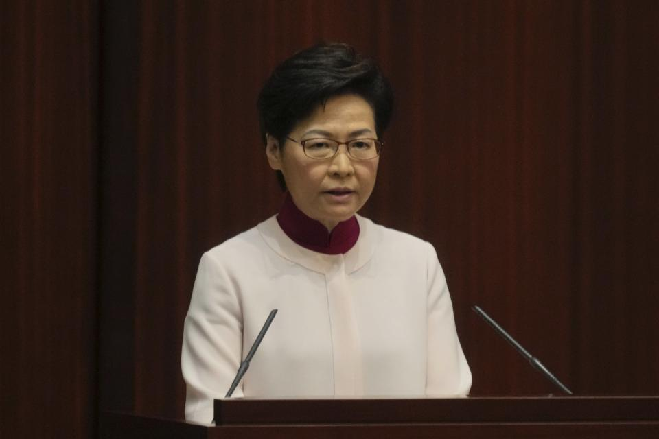 Hong Kong Chief Executive Carrie Lam, center, attends her policy address at the chamber of Legislative Council in Hong Kong, Wednesday, Oct. 6, 2021. Lam announced a major development plan Wednesday for Hong Kong's border area with mainland China in the last annual policy address of her current term. (AP Photo/Kin Cheung)
