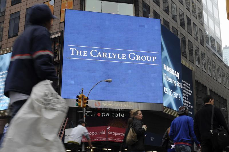 Passersby walk in front of video monitors announcing the Carlyle Group's listing on the NASDAQ market site in New York's Times Square after the opening bell for trading