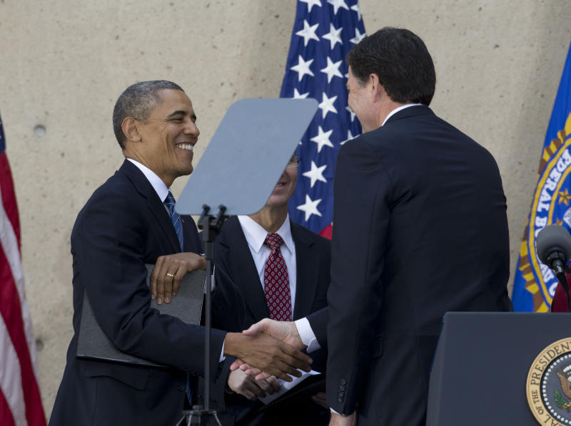 U.S. President Obama shakes hands with FBI Director Comey after he was sworn-in at the FBI headquarters in Washington