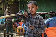 Dansha life: A child with a knife clutches a length of sugar cane
