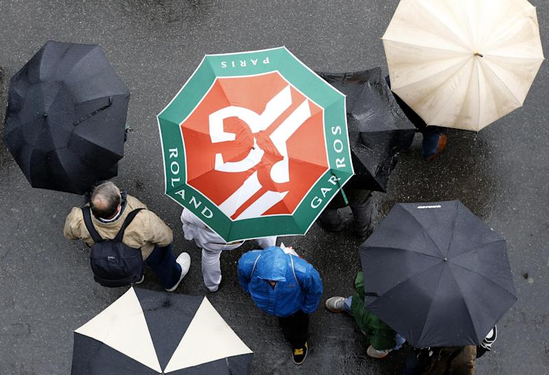 People stroll with umbrellas in the alleys of the Roland Garros stadium as rain delays the start of matches, Tuesday, May 28, 2013 in Paris. (AP Photo/Petr David Josek)