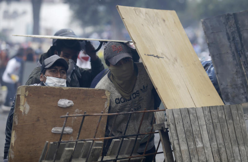 Anti-government demonstrators take cover behind a barricade during clashes with police in Quito, Ecuador, Saturday, Oct. 12, 2019. Protests, which began when President Lenin Moreno's decision to cut subsidies led to a sharp increase in fuel prices, have persisted for days. (AP Photo/Fernando Vergara)