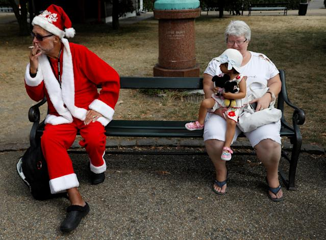 <p>A man dressed as Santa Claus smokes a cigarette before a gathering for the World Santa Claus Congress, an annual event held every summer in Copenhagen, Denmark, July 23, 2018. (Photo: Andrew Kelly/Reuters) </p>