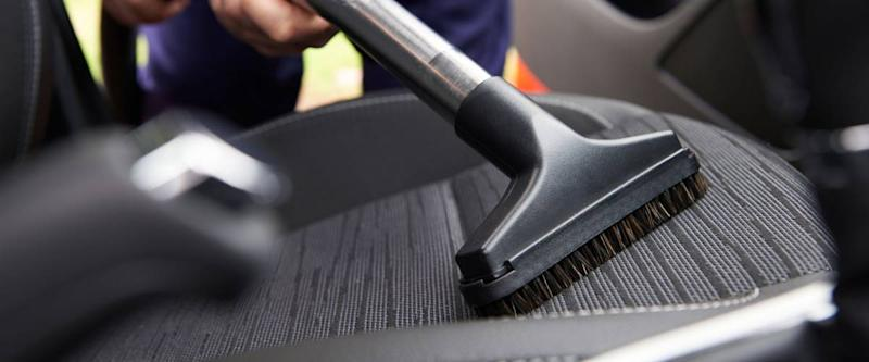 Man vacuuming seat of car