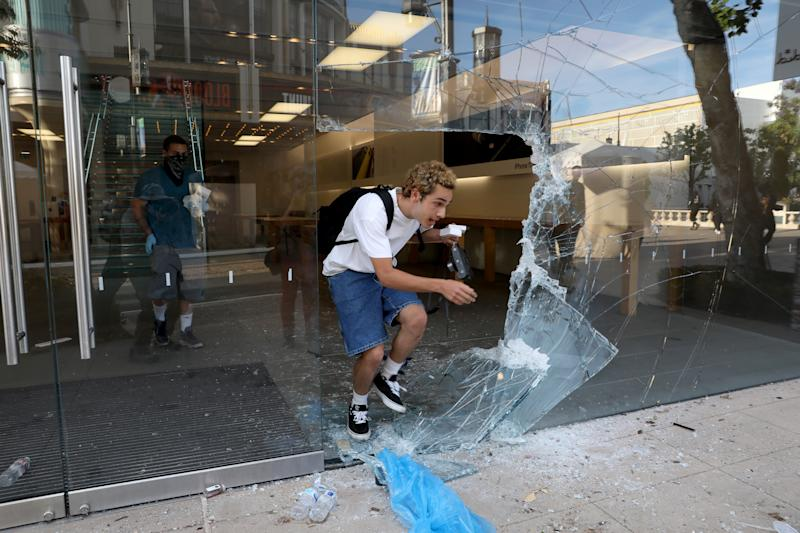 LOS ANGELES, CA -- MAY 30: Looters steal from the Appel Store at The Grove as protestors demonstrate at W 3rd St and S Fairfax Ave. in the Fairfax District on Saturday, May 30, 2020, in Los Angeles, CA. The protestors demonstrate in response to the death of George Floyd in Minnesota. Last night more than 500 arrests after looting and vandalism sweep downtown L.A. (Gary Coronado / Los Angeles Times via Getty Images)