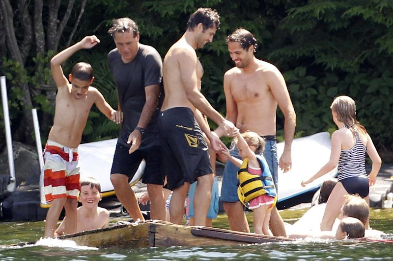 ** ATTN - PLEASE MOVE OVERNIGHT JULY 7 (TONIGHT) WITH STORY EX-WASHINGTON ** FILE - In this July 6, 2012, file photo Republican presidential candidate Mitt Romney, top second from left, plays with family and friends on a floating raft on Lake Winnipesaukee in Wolfeboro, N.H. In an era where non traditional families seem to be the norm, Romney's family stands out because it is traditional. Married for 40 years, five accomplished sons, family vacations etc. This was the portrait of his week at the lake. (AP Photo/Charles Dharapak, File)