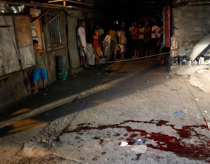Filipino residents view a crime scene after an alleged drug user was shot dead by unidentified gunmen in Parañaque city, south of Manila, on Sept. 27, 2016. (Photo: Eugenio Loreto/EPA)