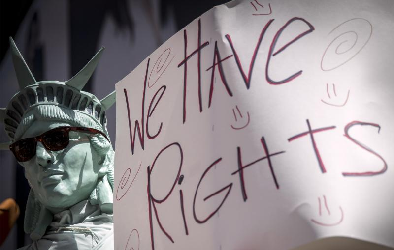 A man dressed as the Statue of Liberty holds a placard during a rally of Costumed Characters in New York's Times Square