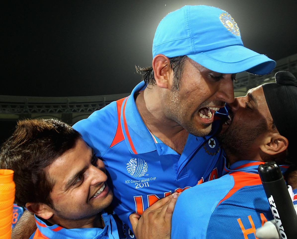 MUMBAI, INDIA - APRIL 02:  MS Dhoni (C) of India celebrates victory with team mates Suresh Raina (L) and Harnhajan Singh after the 2011 ICC World Cup Final between India and Sri Lanka at Wankhede Stadium on April 2, 2011 in Mumbai, India.  (Photo by Hamish Blair/Getty Images)