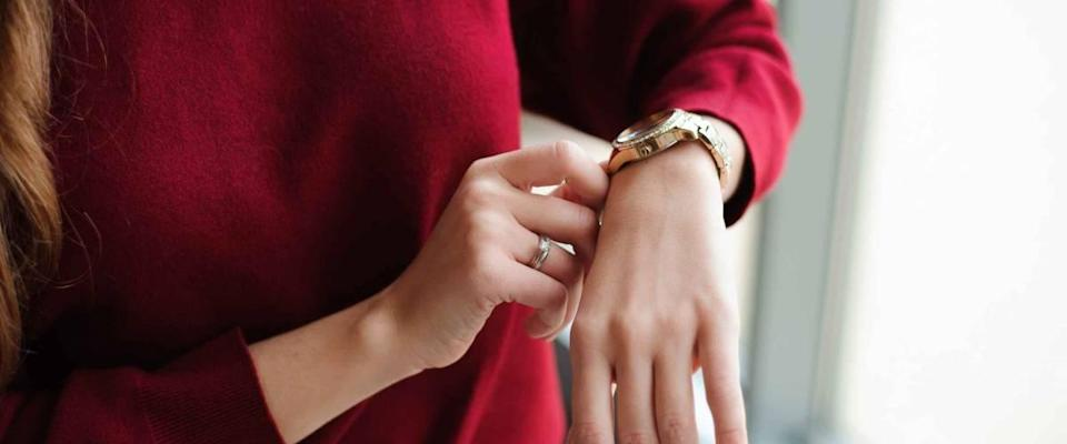 Close up of woman in red sweater looking at watch on her wrist.