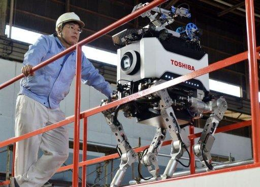 Engineers inspect Toshiba's four-legged robot during a demonstration at Toshiba's technical center in Yokohama, suburban Tokyo. The tetrapod, which weighs 65 kilograms (143 pounds) and is about one metre (3 foot, four inches) tall, is designed to be able to cover difficult terrain -- such as going up steep steps -- that regular robots struggle with