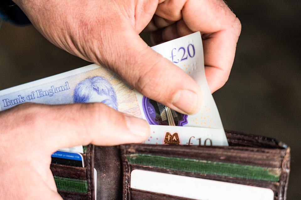 Close-up of a man taking a British twenty pound note out of his wallet.