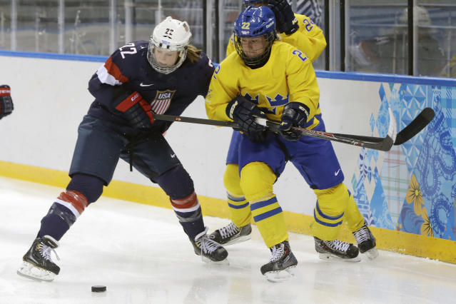 Kacey Bellamy of the United States battles Emma Eliasson of Sweden during the first period of the 2014 Winter Olympics women's semifinal ice hockey game at Shayba Arena Monday, Feb. 17, 2014, in Sochi, Russia. (AP Photo/Mark Humphrey)