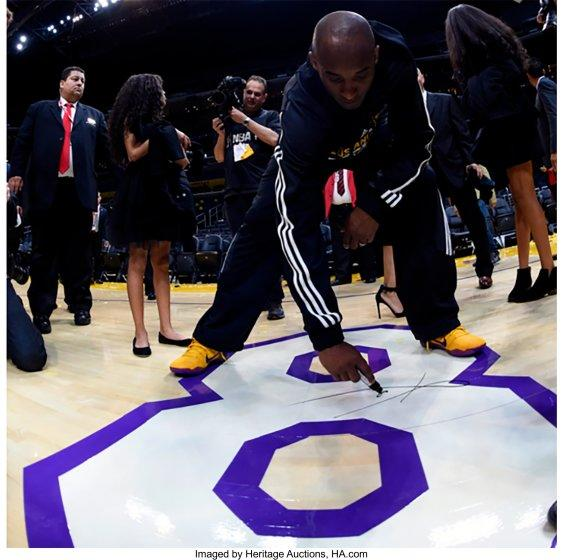 Kobe Bryant signs the No. 8 painted on the Staples Center floor following his final NBA game April 13, 2016.