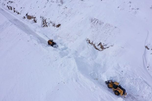 Workers remove snow piled up along the South Klondike Highway on March 2, 2021.